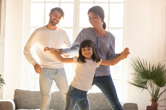 A family dances together in their living room.