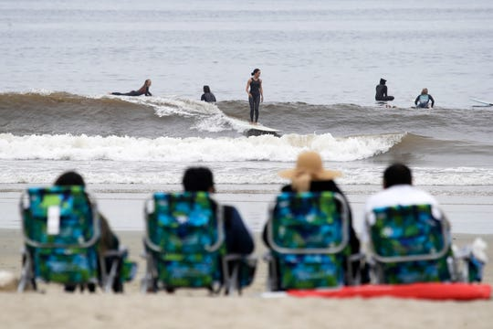 People sit on beach chairs and watch surfers Thursday, April 30, 2020, in Newport Beach, Calif. Gov. Gavin Newsom on Thursday announced that Orange County beaches would be closed until further notice. (AP Photo/Marcio Jose Sanchez)