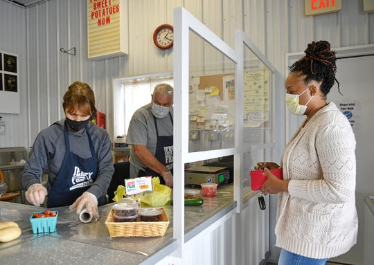 Muzzarelli's Farm Market owner Rita Muzzarelli waits on a customer purchasing fresh produce on Thursday, April 30, 2020. The market recently installed partitions at the cash register to foster physical distancing.