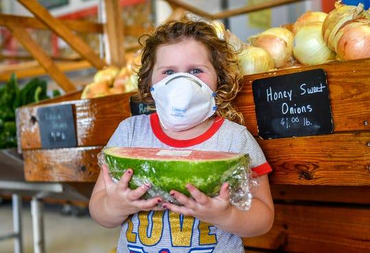 Leah Ryan holds a fresh watermelon at Muzzarelli's Farm Market in Vineland on Thursday, April 30, 2020.