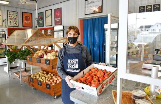 Muzzarelli's Farm Market owner Rita Muzzarelli holds a box of fresh tomatoes at her farm stand on East Oak Road in Vineland on Thursday, April 30, 2020.