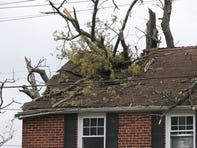 A tree rests partially through the roof of a home on Forest Drive in Forest Brook Glen near Newport as a line of strong winds moved through the area Thursday afternoon.