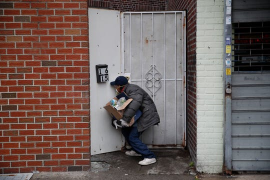 Francisco Ramírez peers through a hole in a fence while looking for an address to deliver a box of groceries to a man in need Saturday, April 18, 2020, in the Queens borough of New York. Some are former construction workers or cleaning ladies who lost their jobs and can barely pay rent, but they go out each day to deliver donated diapers, formula or food to families in need. Through Spanish-speaking chats in Facebook or word of mouth, small groups of immigrants find out who needs the help and they deliver it traveling by car or by foot, exposing themselves to the coronavirus that has already hit hard working-class neighborhoods. (AP Photo/John Minchillo)