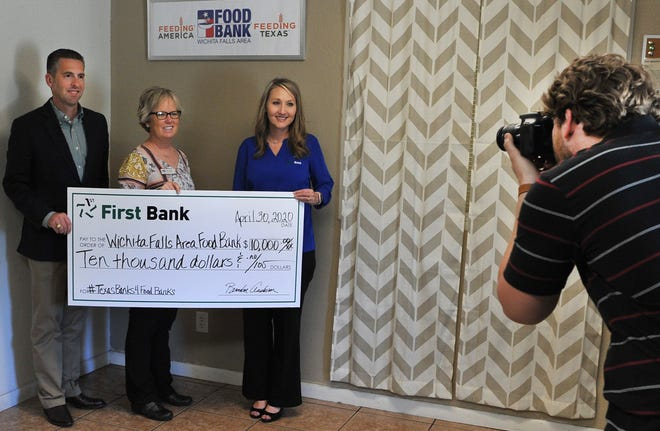 """From left: First Bank, President, Brandon Anderson, Wichita Falls Area Food Bank, CEO, Kara Nicken, and First Bank, marketing director, Amber Gee pause for a picture during a check presentation, Thursday afternoon. First Bank donated $10,000 to the food bank. The donation, according to a press release, is part of the """"Texas Banks 4 Food Banks"""" to raise much-needed funds for food banks around the state."""