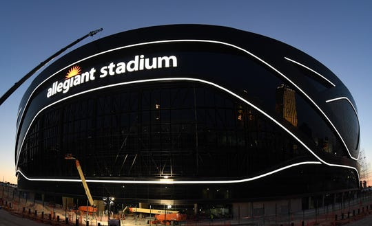 Crews test out architectural light ribbons and exterior sign lighting as construction continues at Allegiant Stadium.