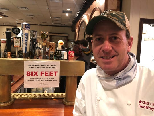"Geoff Tracy, who runs Chef Geoff's in Washington, D.C., stands next to a sign inspired by a frequent diner, Anthony Fauci. Tracy says Fauci and his wife Christine are ""burger and beer"" type patrons, and have stopped by on occasion for take-out during the pandemic."