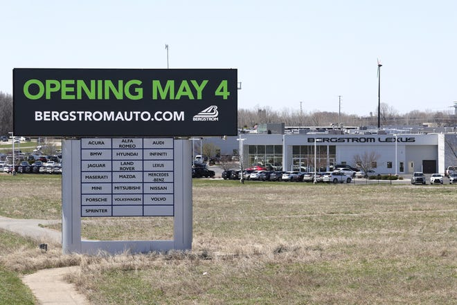 An opening sign is displayed along Interstate 41 in front of Bergstrom Automotive's dealership in Grand Chute.