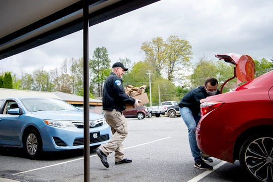 Dave Clancy, and SRO for Waynesville Middle School, helps Nathaniel Stevens, a member of the in-school suspension staff, load a trunk with meals for children at Waynesville on April 30, 2020.