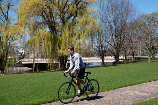 A cyclist peddles past the Battle Creek River on Friday, May1, 2020 in Battle Creek, Mich.