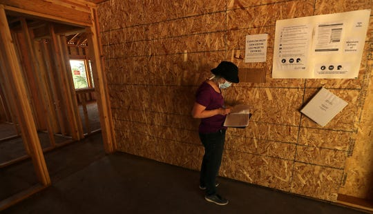 Susan Matan signs into the log book before entering her home that is under construction near Keyport on Friday, May 1, 2020.