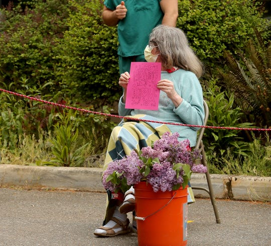 "A Bainbridge Island Health & Rehabilitation resident holds a ""Missing You"" sign during a community parade on Friday."