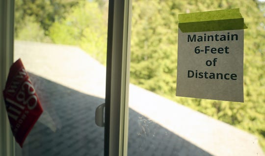 A sign reminding crews to keep 6-feet of distance between each other hangs in the window of Susan Matan's home that under construction in near Keyport on Friday, May 1, 2020.
