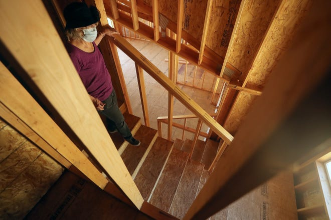 Susan Matan walks down the stairway while she gives a tour of her home that is under construction near Keyport on Friday, May 1, 2020.