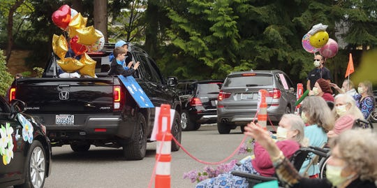 Residents of Bainbridge Island Health & Rehabilitation sit 6 feet apart as they watch a parade of cars drive slowly past them on Friday.