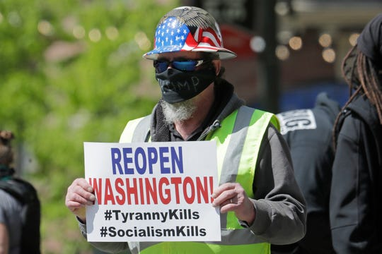 """A person wears a mask that has """"Trump"""" written on it during a protest against Washington state's stay-at-home orders, Friday, May 1, 2020, in downtown Seattle. May Day in Seattle traditionally brings large protests and demonstrations from many groups and causes, and this year some people stayed in their cars or otherwise tried to practice social distancing due to the outbreak of the coronavirus. (AP Photo/Ted S. Warren)"""