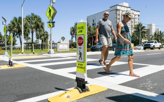 David and Nelsy Ool of Indian Harbour Beach cross A1a Friday afternoon. Crosswalks on A1a have new signage alerting drivers of pedestrians. The improvements along, with a reduced speed limit, are part of changes to the roadway implemented this week. Mandatory Credit: Craig Bailey/FLORIDA TODAY via USA TODAY NETWORK