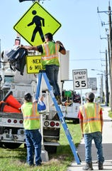 Bobby Spaeth, Tony Flores and Mohamed Talaat  of PowerCorp remove the covers from a pedestrian crossing warning sign on A1a in Satellite Beach Friday. The flashing sign and other improvements, along with a reduced speed limit, are part of changes to the roadway implemented this week. Mandatory Credit: Craig Bailey/FLORIDA TODAY via USA TODAY NETWORK