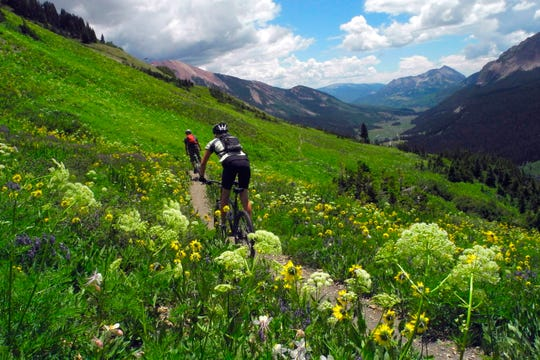 In this July 14, 2013 photo, Shane McDermed, left, of Boulder and Lindsey Samelson of Colorado Springs, ride though the wildflowers on the 401 Trail outside of Crested Butte, Colo. Records reviewed by The Associated Press show that an exclusive group of Texans stood to benefit when the state's attorney general, Ken Paxton, urged the small Colorado county to reverse a public health order during the coronavirus outbreak. Paxton this month told Gunnison County that banning Texans from their property in Colorado during the outbreak was unconstitutional. (Christian Murdock/The Gazette via AP)