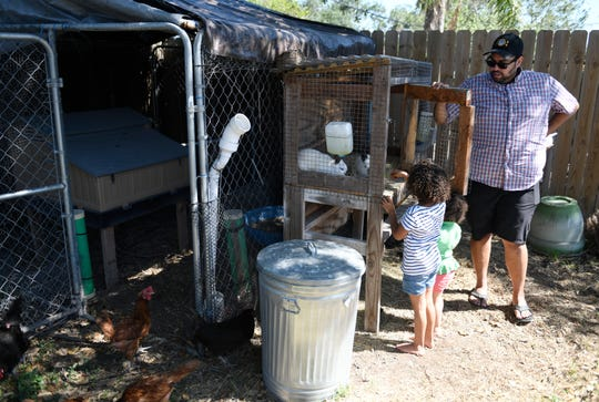 Leo Ruiz, far right, helps his daughters feed the rabbits, Thursday, April 30, 2020. The garden started out as peppers and herbs and has grown to include green vegetables and chickens.