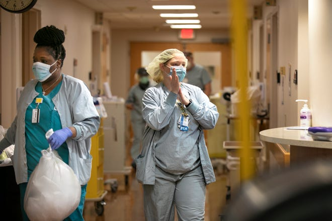 Erica Schmidt, right, patient care assistant at TriHealth Good Samaritan Hospital, works on the COVID floor, Friday, April 24, 2020 at the Clifton, Ohio, hospital.