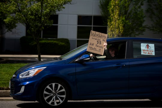 A car passes people protesting the working conditions at the Amazon Fulfillment Center on Friday, May 1, 2020 in Hebron, Kentucky.