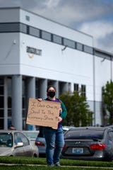 "Sarah Fields, a current Amazon employee, protests the working conditions at the Amazon Fulfillment Center on Friday, May 1, 2020 in Hebron, Kentucky. Fields said, ""People are losing their lives and we are not being protected."""