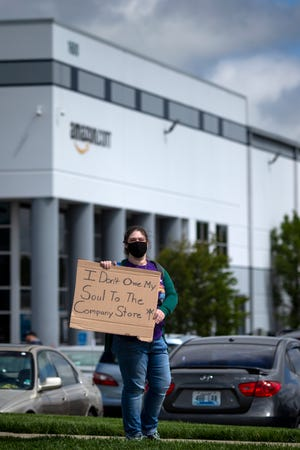 """Sarah Fields, a current Amazon employee, protests the working conditions at the Amazon Fulfillment Center on Friday, May 1, 2020 in Hebron, Kentucky. Fields said, """"People are losing their lives and we are not being protected."""""""