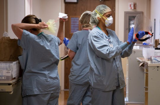 Nurses and patient care assistants clean off personal protective equipment in between seeing patients on the COVID floor.