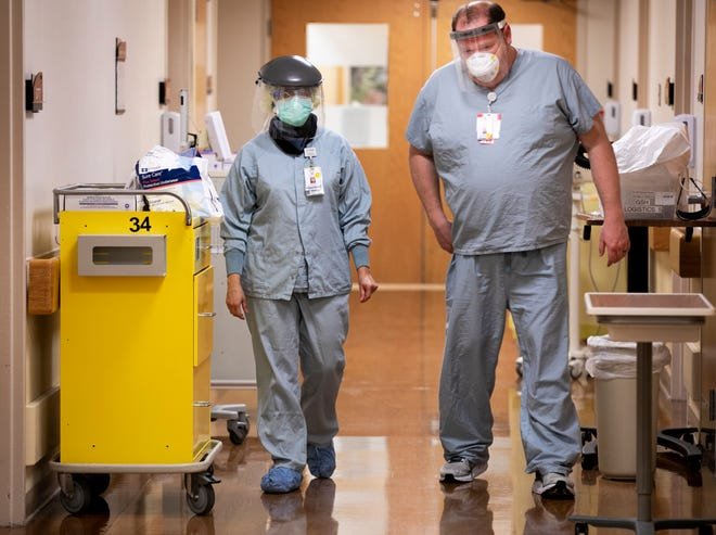 FOR SPECIAL PACKAGE: Dr. Anjum Nageed, left, and Steve Blessinger, nurse, at TriHealth Good Samaritan Hospital discuss a patient on the COVID floor after Nageed exited the room, Friday, April 24, 2020. Good Sam, as it's known, is located in Clifton, Ohio.