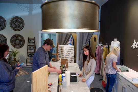 Gabe Hockman, left, checks out with Jennyann Stokes at Re:defined Boutique in Clarksville, Tenn., on Friday, May 1, 2020.