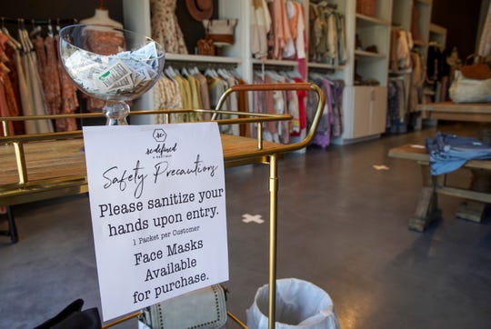 A sanitation station rests at the front entrance where customers can sanitize their hands before browsing goods at Re:defined Boutique in Clarksville, Tenn., on Friday, May 1, 2020.