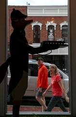 Passersby walking up Franklin Street look in at the fox statue presenting whiskey at Journey's Eye Studio in Clarksville, Tenn., on April 29, 2020.