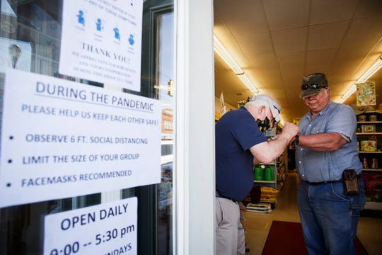 Dave Trask, left, works on the watch of Steve Neal, right, of Pitzer on the sidewalk outside of Ben Franklin on Friday, May 1, 2020, in Winterset. Neal said his watch broke a week ago and once he heard that the store was back open he came in as soon as he could. The store is one of the few outlets in select Iowa counties allowed to open back up at 50% capacity.