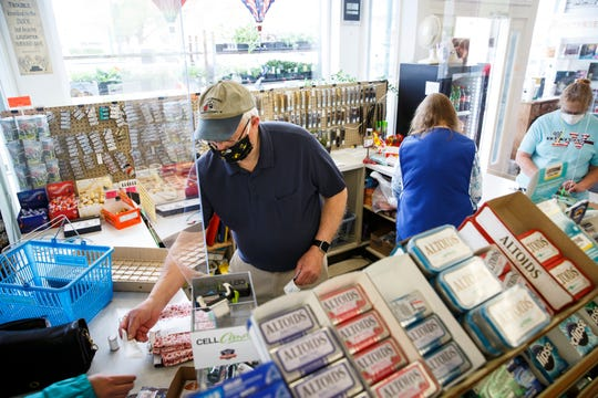 Dave Trask, owner of the Ben Franklin store checks out a customer under a piece of plexiglass on Friday, May 1, 2020, in Winterset. Starting Friday, Gov. Kim Reynolds allowed restaurants, retail shops, libraries, gyms and malls in 77 countiesÊwhereÊcoronavirus activity has been minimalÊor declining to reopen. Those businesses can only operate at 50% capacity and must adhere to social distancing and sanitation guidelines.