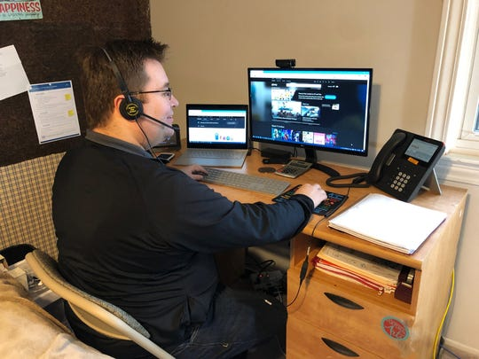 Comcast retail sales associate Chuck Oliver answers customer calls from his makeshift home office.
