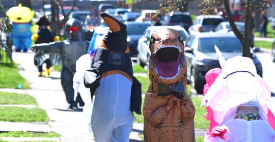 Characters walk in line as members of the Ferndale T-Rex Walking Club put on their inflatable costumes and walk around the south end of Ferndale on Friday, May 1, 2020.