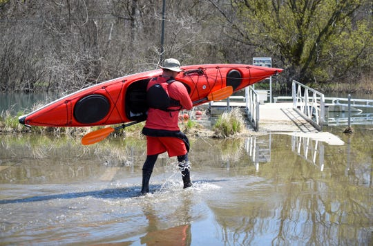 Doug Minidis of Woodhaven, carries his kayak through a flooded parking lot as he prepares to use the kayak launch at Elizabeth Park in Trenton, May 1, 2020.
