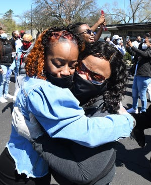 Lorenzo Seldon's wife, Renaye, left, gets a hug from sister-in-law Keisha Burnett during a memorial service Friday for Lorenzo, a union steward at Fiat Chrysler's Warren Truck plant who died of COVID-19.