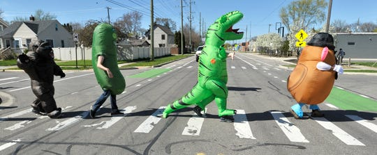 Characters walk on Spencer as they cross Hilton. Members of the Ferndale T-Rex Walking Club put on their inflatable costumes and get exercise while walking around the south end of Ferndale on Friday, May 1, 2020.