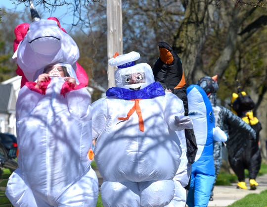 Members of the Ferndale T-Rex Walking Club put on their inflatable costumes and walked around the south end of Ferndale on Friday, May 1, 2020.