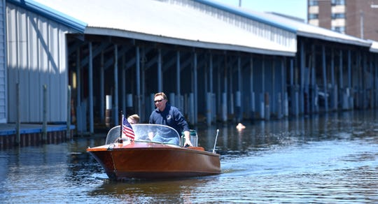 Dave Miller instructs his son, Owen, 14, both of St. Clair Shores, as they take their maiden voyage on their 1955 Clyde Runabout vessel that was made in Detroit. They were at the Blossom Heath Boat Launch and Piers in St. Clair Shores, May 1.