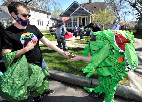 Mike Crimando, left, hands a cell phone back to his wife, Keely, both of Ferndale, as they put on their T-Rex costumes.