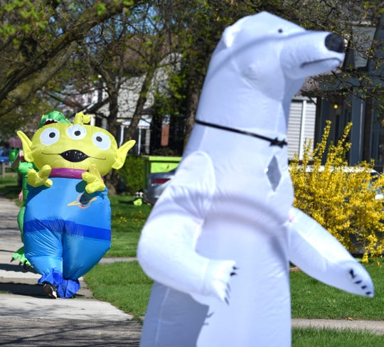 Characters follow each other through the neighborhoods as members of the Ferndale T-Rex Walking Club put on their inflatable costumes and walk around the south end of Ferndale on Friday, May 1, 2020.