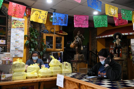 From left, head cashier Analicia Lopez fills carry out orders while Alexandra Garcia takes orders on the phone at Taqueria Mi Pueblo in Detroit on April 30, 2020. The restaurant has been closed since the coronavirus outbreak but opened this week for carry out business, just in time for Cinco de Mayo.