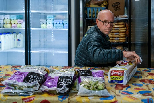 Lord's Pantry President Joe Hopf stores leftover bread and salad packages into a refrigerator at Lord's Pantry in Fort Branch, Ind., Wednesday, April 15, 2020. The food pantry, which serves the Fort Branch and Haubstadt communities, is open from 9 a.m. to noon on Wednesdays and is currently only providing drive-up service due to safety concerns over the COVID-19 pandemic.