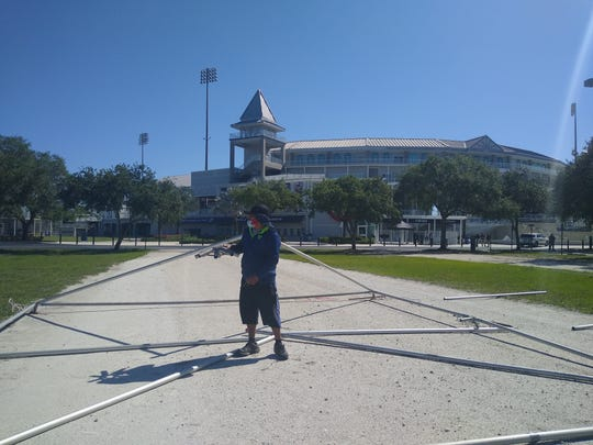 A worker sets up support structure for a tent in the parking lot of Hammond Stadium in Lee County. The stadium parking lot will be the site of free coronavirus testing beginning Monday.