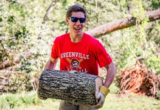 GHS baseball player Braden Golinski  carries logs to the road. Greenville High baseball players, parents and coaches came to help Rick Richardson (Greenville High class of 1970) Friday, May 1, 2020, whose home and property were damaged by a recent tornado.
