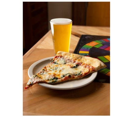 A slice of pepperoni and spinach pizza with a Sierra Nevada Hazy Little Thing