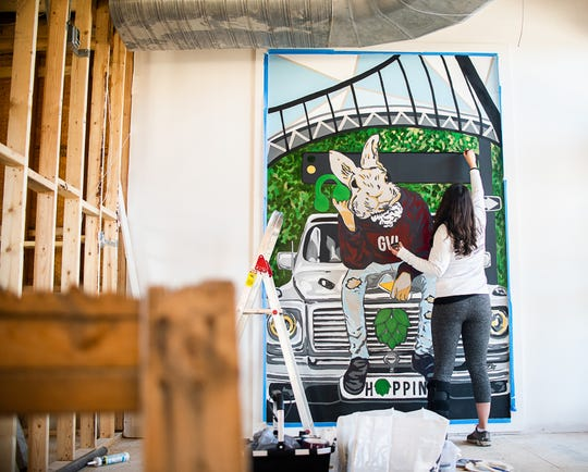 Lacey Hennessey works on a mural at Hoppin' in downtown Greenville.
