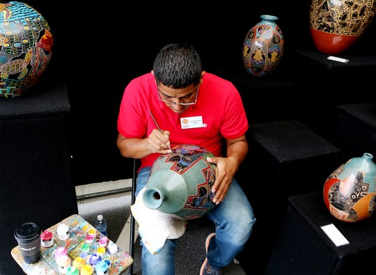 Artist Luis Enrique Gutierrez puts finishing touches on a ceramic pot during Artipshere in downtown Greenville on Saturday, May 13, 2017.